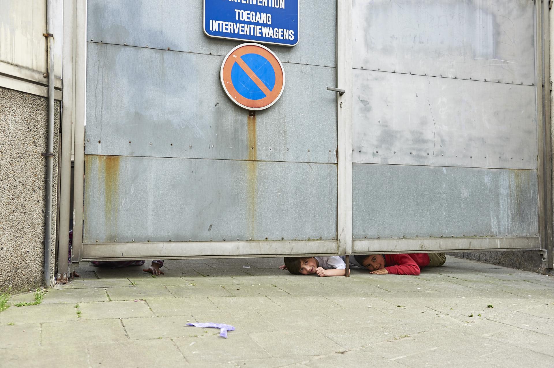 Schaerbeek, Brussel, kinderen gluren onder de poort van het schoolplein door