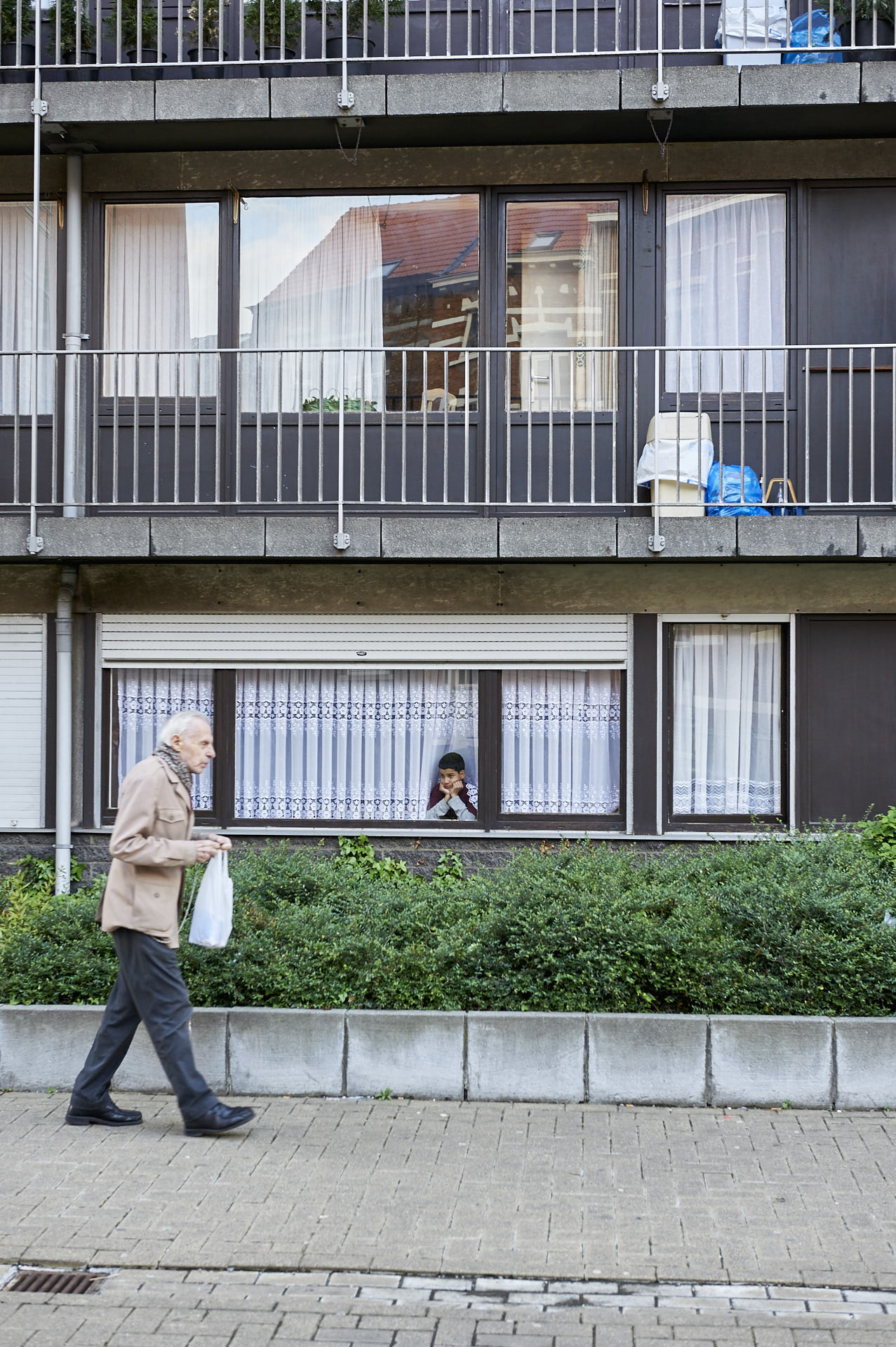 Schaerbeek, Brussel, oude man met tasje, jongen kijkt van achter het raam, fotografie ,Frank Penders