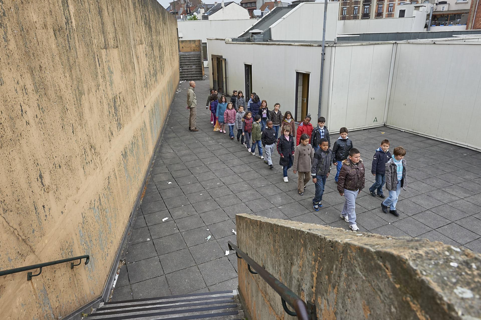 Schaerbeek, Brussel, schoolplein , kinderen marcheren, leraar kijkt toe