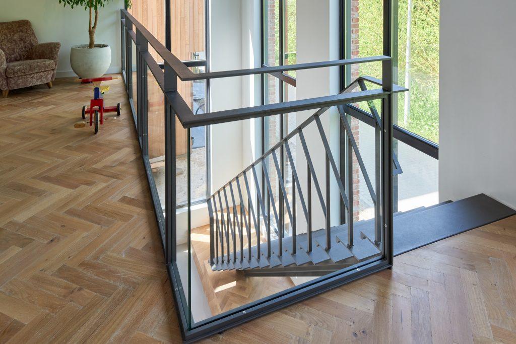 Stalen grijze design trap met een middenboom en stalen leuning. Glazen balustrade bij de vide en eikenhouten visgraat vloer.