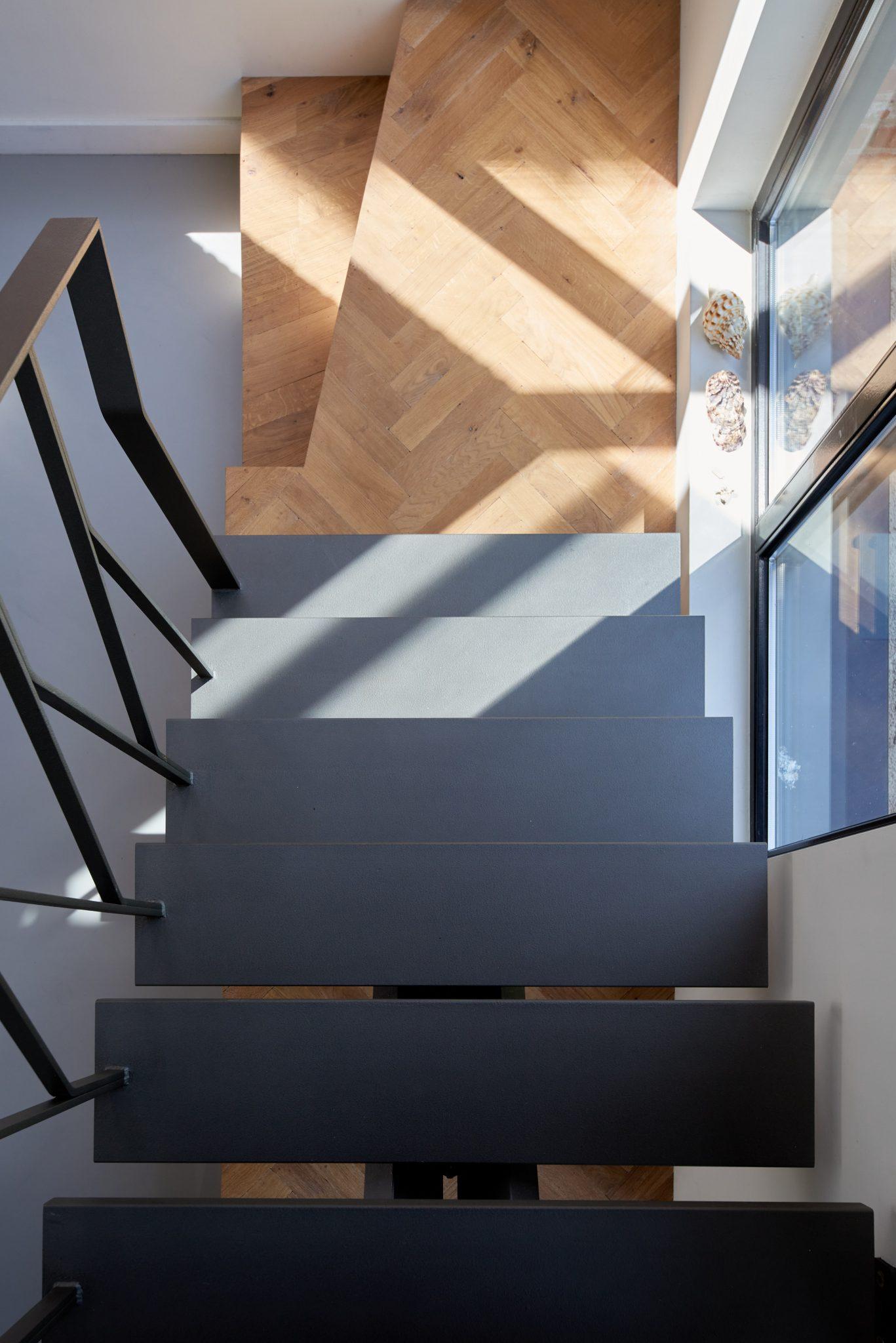 Stalen grijze design trap met een middenboom en stalen leuning. Eikenhouten visgraat vloer.