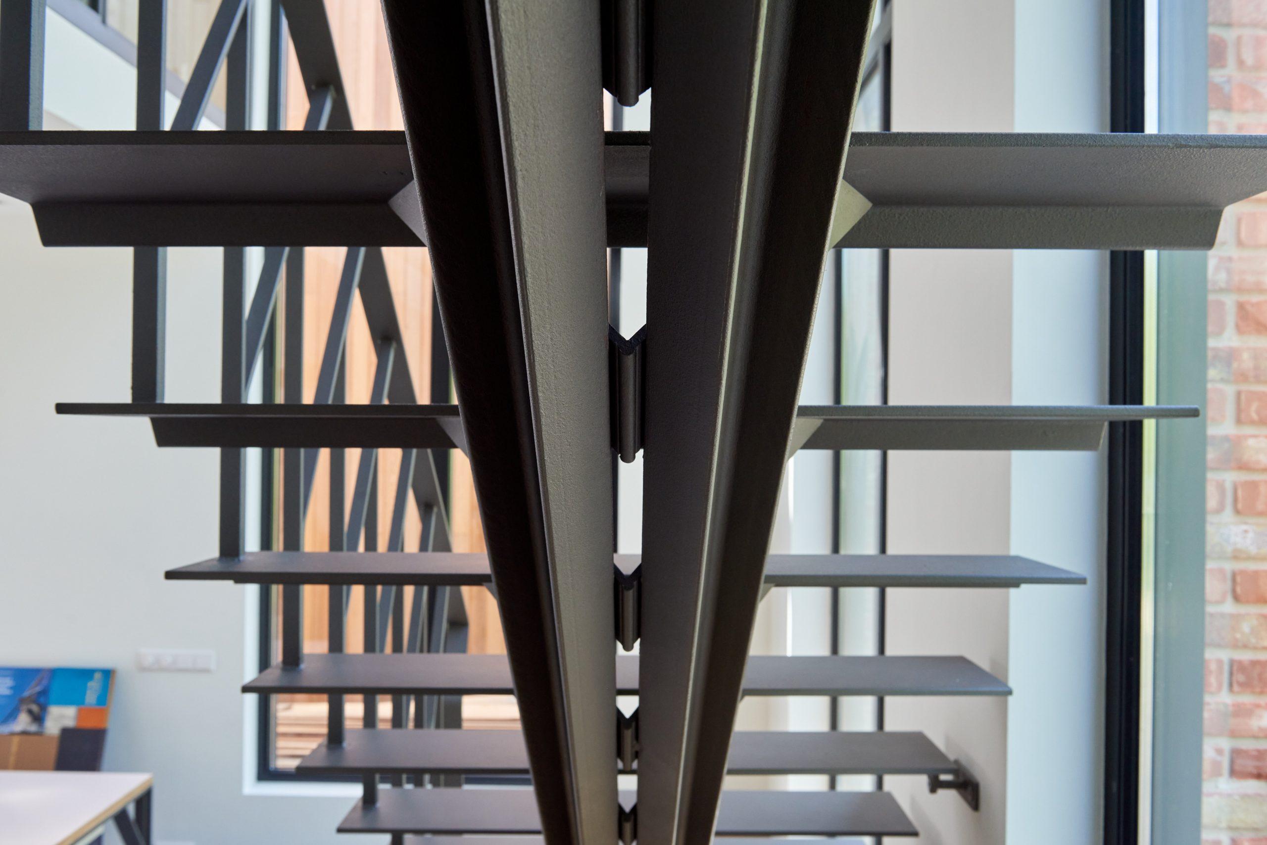 Stalen grijze design trap met een middenboom en stalen leuning. Zwevende treden.