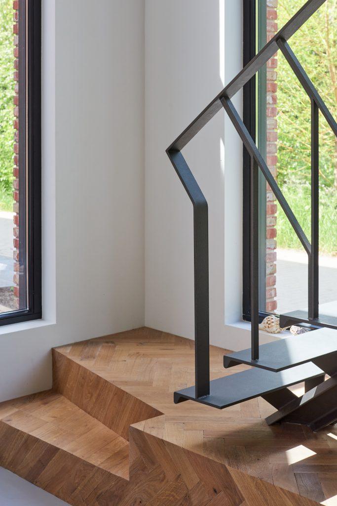 Stalen grijze design trap met een middenboom en stalen leuning. Gebogen staal. Zwevende treden.