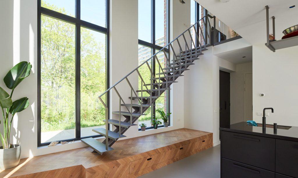 Stalen grijze design trap met een middenboom en stalen leuning. Woonkeuken met kookeiland. Eiken houten visgraat vloer op bordes