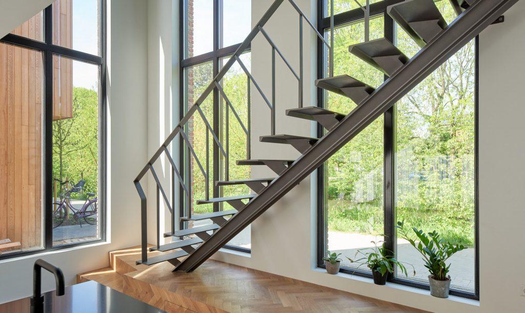 Stalen grijze design trap met een middenboom en stalen leuning. Villa te Amsterdam.