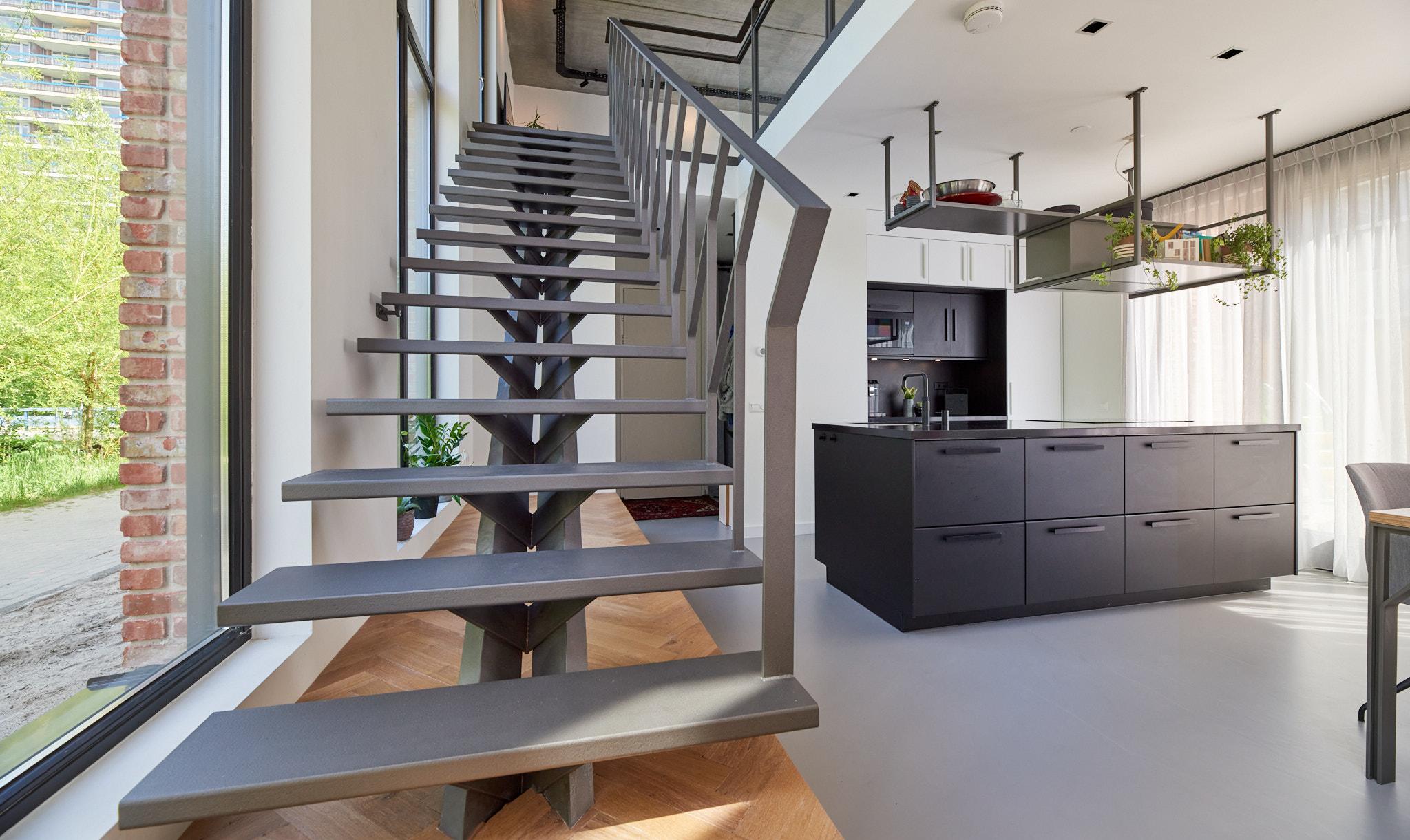 Stalen grijze design trap met een middenboom en stalen leuning. Woonkeuken met kookeiland.