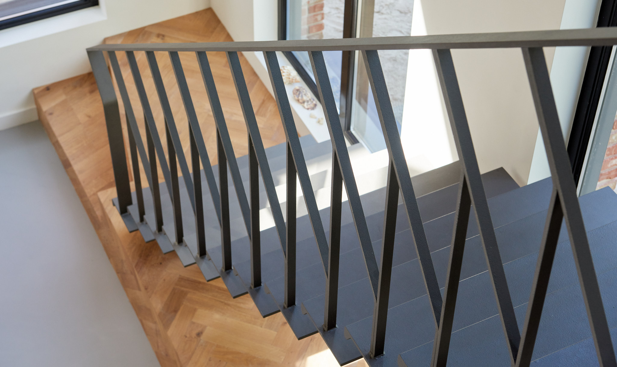 Stalen grijze design trap met een middenboom en stalen leuning. Eikenhouten visgraatvloer.